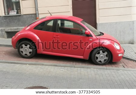 PRAGUE, CZECH REPUBLIC - CIRCA SEPTEMBER 2015: red Volkswagen New Beetle car parked in a street of the city centre.  - stock photo