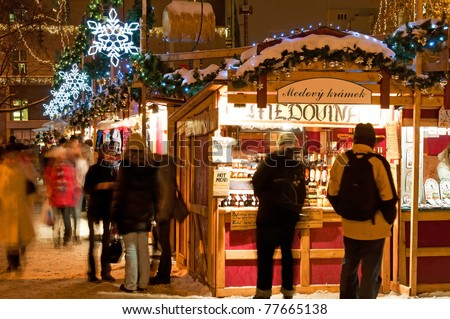 PRAGUE, CZECH REPUBLIC - DECEMBER 17: Group of people enjoy Christmas market in Prague on December 17, 2010. It attracts more than 750 thousands of visitors during the whole advent time. - stock photo