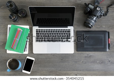 Prague, Czech Republic - DECEMBER 20, 2015: Photo of photografer desk. IPhone 6, Macbook and iPad  are produced by Apple Computer, Inc.. Tablet are produced by Wacom. Camera are produced by Canon.