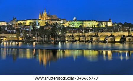 Prague, Czech Republic. Evening view of the Prague Castle with St. Vitus Cathedral, Castle district, Mala Strana district with St. Nicholas Church, and Charles Bridge with Mala Strana Bridge Towers. - stock photo