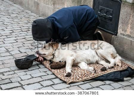 PRAGUE, CZECH REPUBLIC - FEBRUARY 13, 2016:  Kneeling man and his dog begging on the Charles Bridge - stock photo