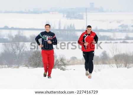 PRAGUE, CZECH REPUBLIC - FEBRUARY 24, 2013: Two men run on the snow track. - stock photo