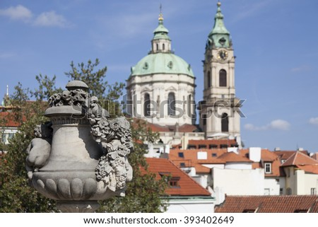 Prague, Czech Republic. Focus on foreground sculpture with blurred image of St. Nicholas Church in the background.