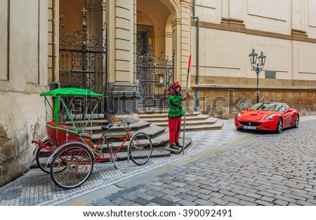 Prague, Czech Republic - January 16, 2015:  Bicycle rickshaw, a sports car and a street performer in front of an art nouveau building with an ornate gate in old town Prague