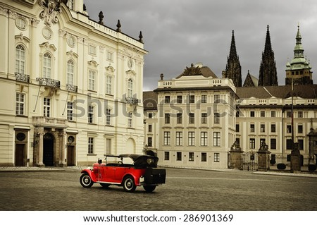 PRAGUE, CZECH REPUBLIC - JULY 17, 2012: Red Color Retro Car on the Hradcany Square (Hradcanske namesti). Retro Stylized Image. - stock photo