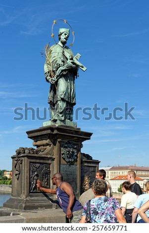 PRAGUE, CZECH REPUBLIC - JULY 3, 2014: The statue of St. John of Nepomuk on Charles bridge - the oldest one on the bridge. Touching it brings good fortune and ensures returning to the city of Prague.  - stock photo