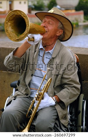 PRAGUE, CZECH REPUBLIC   JUNE 14, 2008: Famous in Prague stiff-limbed street musician plays jazz on the Charles bridge in the capital of Czechia Prague while sitting on the wheel chair - stock photo
