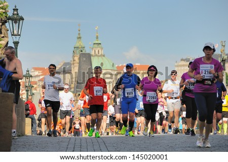PRAGUE, CZECH REPUBLIC - MAY 12: Group of runners runs the Volkswagen Prague Marathon, May 12, 2013 in Prague, Czech republic. Runners run over the Charles Bridge, the famous place in Prague.