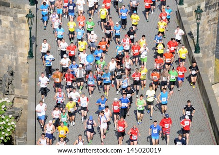 PRAGUE, CZECH REPUBLIC - MAY 12: Group of runners runs the Volkswagen Prague Marathon, May 12, 2013 in Prague, Czech republic. Runners run over the Charles Bridge, the famous place in Prague. - stock photo