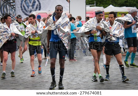 PRAGUE, CZECH REPUBLIC - MAY 3, 2015: Runners who have just finished the Volkswagen Prague Marathon wrapped in aluminum foil walking from the finish of the marathon in the Old Town Square - stock photo
