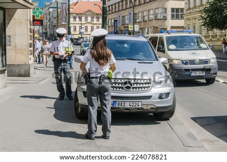 PRAGUE, CZECH REPUBLIC - MAY 10, 2011: Two policemen prescribed fee for parking on the street of Prague on 10 May 2014. - stock photo