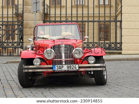 Prague, Czech Republic - November 9, 2014: Red Alfa-Romeo retro car waiting for the next customer to entertain. These cars are usually rented by the tourists visiting Prague. - stock photo