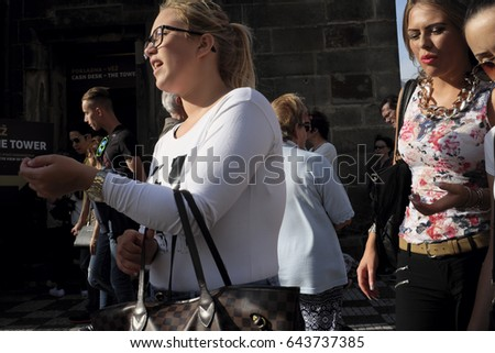 Prague, Czech Republic - October 13: The girls go down the street around the astronomical clock and the sun shining into their faces on October 13, 2015 in Prague, Czech Republic.