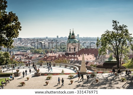 PRAGUE, CZECH REPUBLIC - OCTOBER 10, 2015: Tourists at viewpoint in Prague: city view and St. Nicholas church - stock photo
