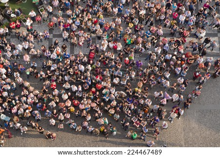 PRAGUE, CZECH REPUBLIC - SEPTEMBER 9, 2014: Aerial Top View Large group of tourists at Prague central square looking up to Old Town Hall tower. - stock photo
