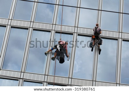 PRAGUE, CZECH REPUBLIC - SEPTEMBER 5, 2015: Two rope access workers clean windows in an office building in Charles Square in Prague, Czech Republic.  - stock photo
