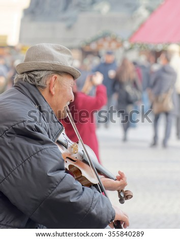 PRAGUE, CZECHIA - DEC 04, 2015: Side view of old man playing the violinin in a public square, tourists in the background. December 04, 2015 in Prague, Czechia - stock photo
