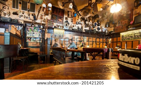 PRAGUE - JUNE 15: People drink beer inside the czech restaurant U SADU with many details, musical instruments and used things on ceiling on June 15, 2014. Prague receives 4.4 million visitors annually - stock photo