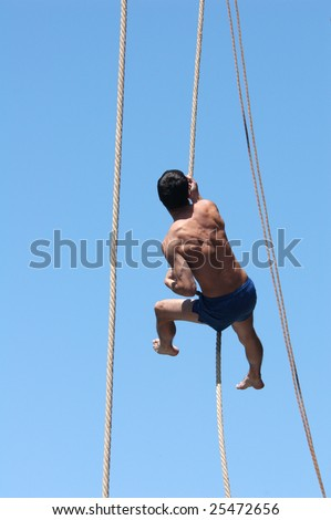PRAGUE, JUNE 17 - Shirtless athlete climbing up the rope during a rope-climbing competition in Prague, Czech Republic, on June 17, 2008