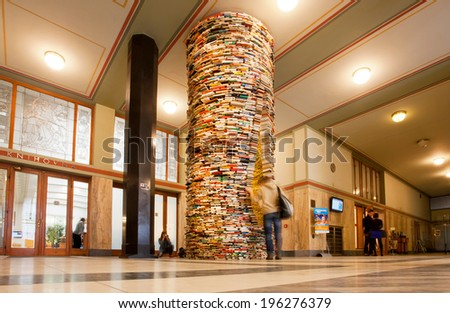 PRAGUE - JUNE 14: Student watching the unreal books tower in the hall of Municipal Library on June 14, 2014 in Czech Republic. Prague's Library has 344,000 books and 2 mobile libraries - stock photo