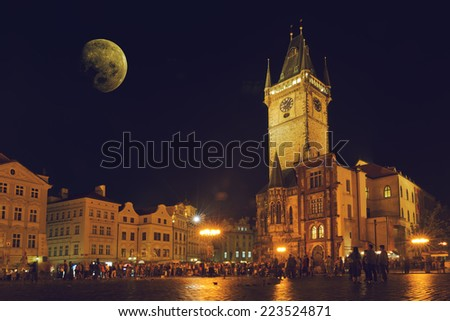Prague Old Town Hall at Night with unrecognizable tourists walking - stock photo