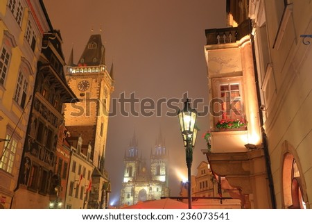 Prague Old Town with Old Town Hall and Astronomical Clock and distant Church of Our Lady before Tyn in foggy autumn night, Czech Republic - stock photo