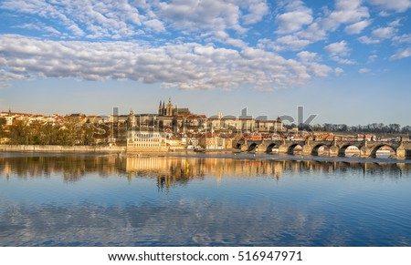 Prague skyline and water reflection - Colorful cityscape with the Charles Bridge, the Vltava river and Prague's buildings, under a blue sky, dotted with clouds and reflected in the water.