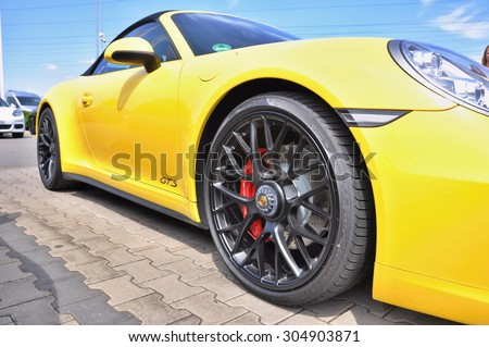 PRAGUE, THE CZECH REPUBLIC, 02.08.2015 - Closeup of luxury yellow Porsche 911 Carrera 4 GTS parking in front of a car store - stock photo