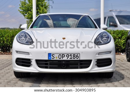 PRAGUE, THE CZECH REPUBLIC, 02.08.2015 - New white Porsche Panamera parking in front of car store Porsche Prosek Prague - stock photo