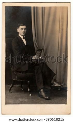 PRAGUE, THE CZECHOSLOVAK REPUBLIC - CIRCA 1920s: Vintage photo shows young man sits on armchair. Antique black & white studio portrait. - stock photo