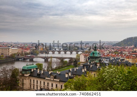 Prague view with a river and bridges from hill with park Letensky garden. Gloomy weather.