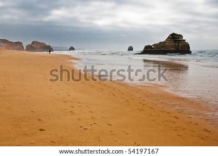 Praia da Rocha on the Atlantic Ocean in Algarve, southern Portugal in the morning, before sunrise. - stock photo