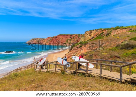 PRAIA DO AMADO BEACH, PORTUGAL - MAY 15, 2015: surfers walking on footbridge from beautiful beach in Algarve region. Surfing is popular sport in south western Portugal due to frequent strong winds. - stock photo