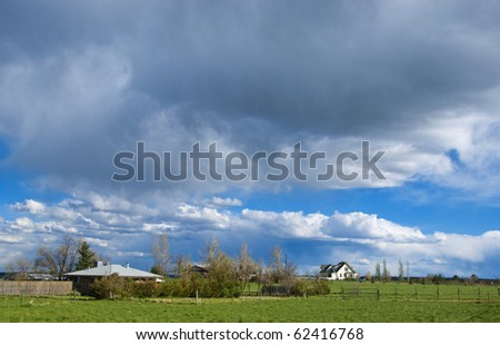 Prairie farms and ranches rest in sunlight under brewing storm clouds with distant rain, on the Colorado plains. - stock photo