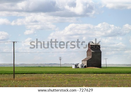 Prairie landscape with an old grain elevator - stock photo
