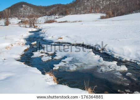 Prairie Stream in Winter:  An icy stream flows across snowy farmland on a cold day in southern Wisconsin.  - stock photo