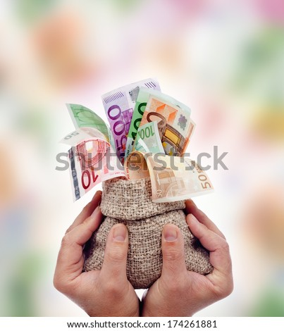Praising money concept - male hands holding bag of euro banknotes - stock photo