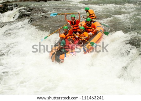 "PRAJINBURI,THAILAND-AUGUST 19 : "" Ekra"" team in action at Rafting racing Hinperng's got challenge 2012 on Saiyai river in Khao Yai National park on August 19,2012 in Prajinburi,Thailand. - stock photo"