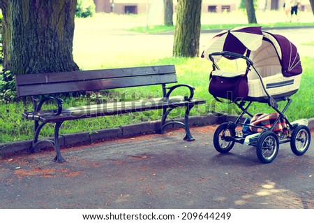 Pram in the park with a bench - stock photo