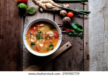 """Prawn soup with mushroom or """"Tom Yum Goong"""" is the most famous of all Thai soups,Tom Yum Soup and Ingredients on old wood. - stock photo"""