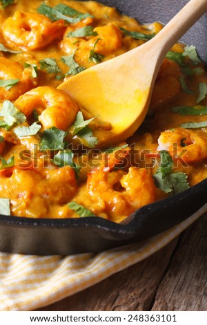 Prawns in curry sauce in a black frying pan macro. vertical, rustic style