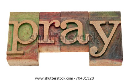 pray word in vintage wooden letterpress printing blocks, stained by color inks, isolated on white