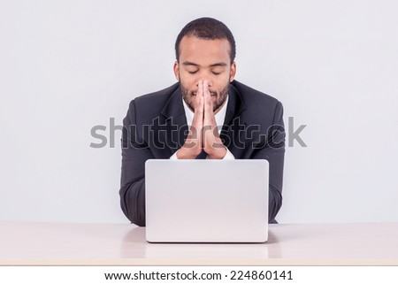 Prayer at work. Smiling African businessman sitting at a desk on a laptop while a businessman sitting at a table and  holding his hands behind his head on isolated gray background - stock photo