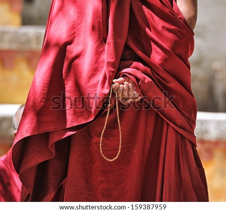 Prayer beads in monk's hand - stock photo