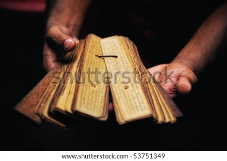 Prayer book of papyrus in the hands of Buddhist monk