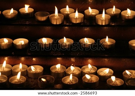 Prayer candles aka offering, votive or memorial candles lit in a dark church - stock photo