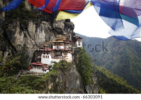 Prayer flags above the sacred Tatkshang Lhakang, Bhutan. - stock photo