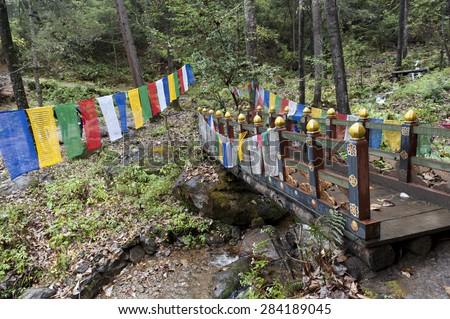 Prayer flags with a footbridge at Taktsang Monastery, Paro Valley, Paro District, Bhutan - stock photo