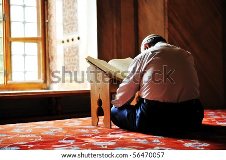 Prayer in mosque, reading Koran - stock photo