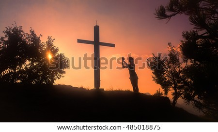 Prayer of a woman under a cross in a red sunset